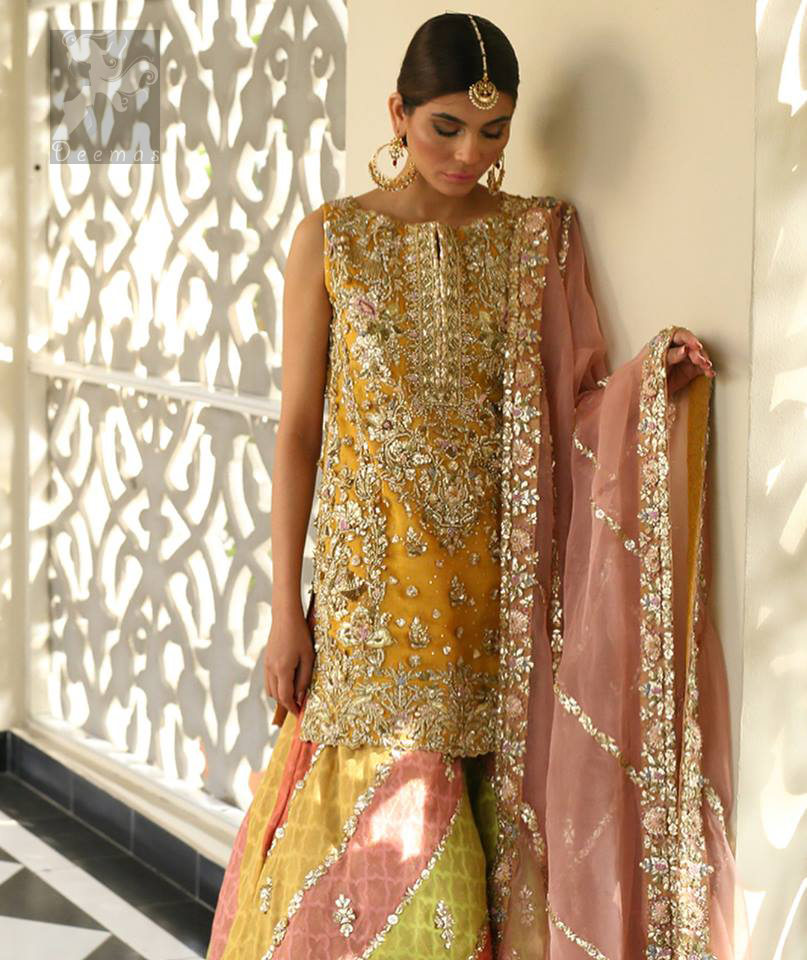 Amber shirt adorned with mainly light golden embellishment on neckline, hemline and side slits. Pink peach dupatta adorned with embellished border and stripes. Multiple color sharara adorned with border on hemline, stripes and motifs.