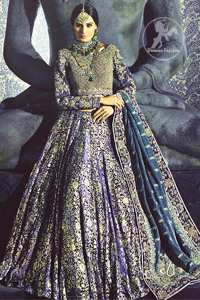 Violet Blue Blouse is of velvet fabric. It is heavy embellished full sleeves blouse featuring antique and golden shaded kora, dabka, resham, naqshi, pearls, crystals and swarovski. Blouse is fully scalloped with blue bayoux resham outline. Sleeves are adorned with floral work and sprinkling sequins/naqshi on it, while bodice having criss cross pattern all over it. It comes with raw silk lehengha which is adorned with block printing and the touch of hand embellishment. It is artistically coordinated with blue bayoux dupatta which is adorned with fully embellished appliqued borders. Borders are accompanied by delicate work along its internal sides. There are four embellished heavy flowers on corners and small floral pattern all over it.