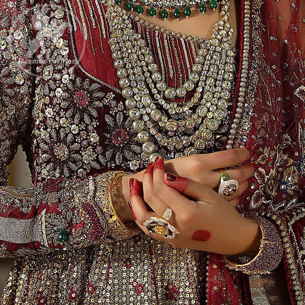 This maroon angrakha frock heavily embellished in the front with silver gold kora dabka, kundan and stones work. One side shoulder neckline is beautifully ornamented with sequins lines in geometric manner. Paired up with matching brocade sharara which looks so magnificent. This outfit is meticulously coordinated with maroon dupatta with embellished borders on lengths.