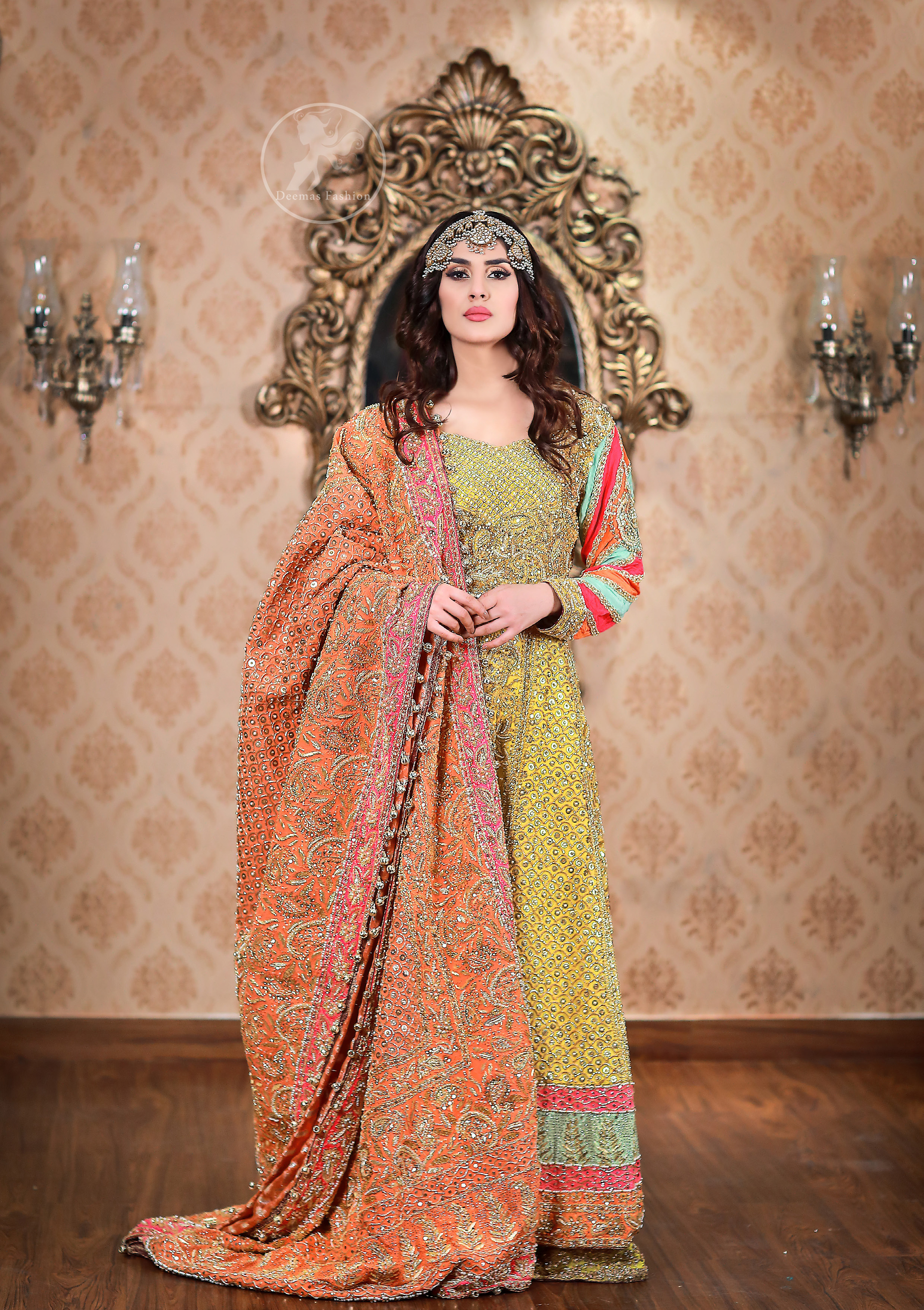 This outfit is decorated with antique shaded embroidery. The dress is fully embellished. Sleeves are decorated with different colour applique which adds to the look. It is adorned with thick embellished appliqued borders. It comes with yellow sharara and sequins spray all over it . It is coordinated with orange raw silk heavy embellished dupatta which has embellished with pink appliqued borders and beautiful tassels.