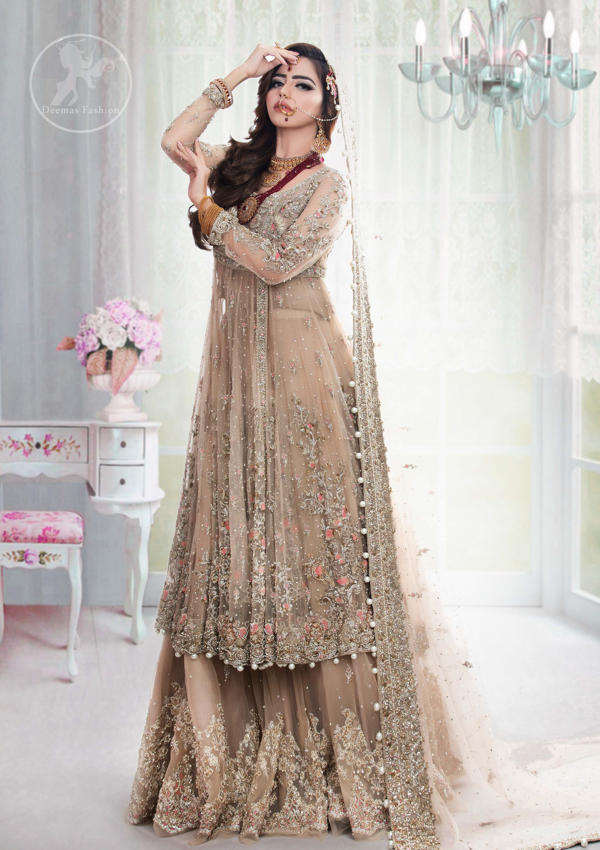 This outfit is meticulously featuring antique shades of kora, dabka, tilla, sequins and pearls. This dress is beautifully sculptured with floral embroidery. Angrakha is decorated with tassels which adds to the look. It is adorned with scalloped border. It comes with heavy embellished lehengha which has been adorned with large border on hemline. It is artistically coordinated with embellished dupatta.