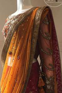 This dress is beautifully sculptured with floral embroidery. It is adorned with intricate detailing embellishment with antique gold kora dabka, tilla, kundan and swarovski. The blouse has full length sleeves decorated with floral motifs. It is coordinated with hot pink banarsi lenhengha finished with golden gota lace at the bottom. It is enhanced with floral motifs. The outfit is beautifully coordinated with orange pallu style dupatta embellished with golden Gotta lace on all sides.