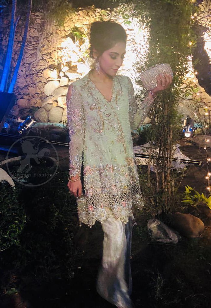 This short frok is decorated with thread, kora, dabka, tilla, sequins and swarovsky. It is embellished with floral thread embroidery. Sleeves are fully embroidered and adorned with cold shoulder design. It is decorated with intricate cutwork on hemline. It is further enhanced with embroidered scalloped border on hemline which adds to the look. It comes with brocade bell shaped pants. It is beautifully coordinated with chiffon dupatta which is sprinkled with sequins all over it.