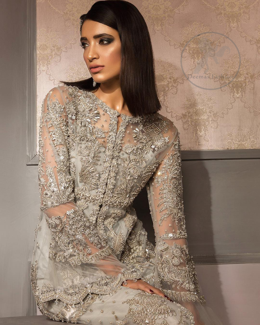 This beautiful gown is decorated with resham thread, kora, dabka, tilla, sequins and pearls. It is sculptured with floral thread embroidery. Sleeves are bell shaped and fully embroidered. It comes with brocade straight trouser. It is beautifully coordinated with organza dupatta.