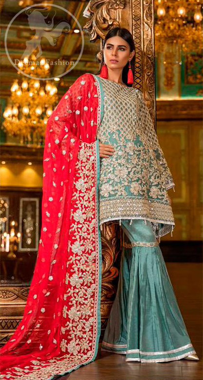 This shirt is adorned with floral embroidery.It is allured with silver and white kora dabka, tilla, sequins and swarovski. This outfit is decorated with intricate cut-work pattern on bodice and sleeves as well. It is beautifully paired up with blue smoke gharara pants. It is artistically coordinated with torch red dupatta which has one sided heavy embroidery and sprinkled with sequins all over it.