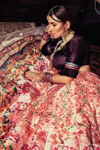 This outfit is a timeless beauty. Dark purple self-printed blouse is decorated with applique. The raw silk classic lehenga is adorned with digital print. Its floral print is further decorated with swarovski, tilla, kora dabka. Its beautiful printed border adds to the look. This outfit is beautifully coordinated with peach pink dupatta with heavy embroidered borders.