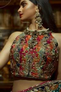 This outfit is a timeless beauty. It is heavily embellished with antique gold kora, dabka, tilla, sequins and swarovski crystals. This exquisite halter neckline blouse is fully decorated with floral motifs patterns all over it. Applique waist belt is decorated with gota and thread embroidery.It comes with embellished lehengha. This Outfit is beautifully coordinated with lime green dupatta with heavy embroidered borders.
