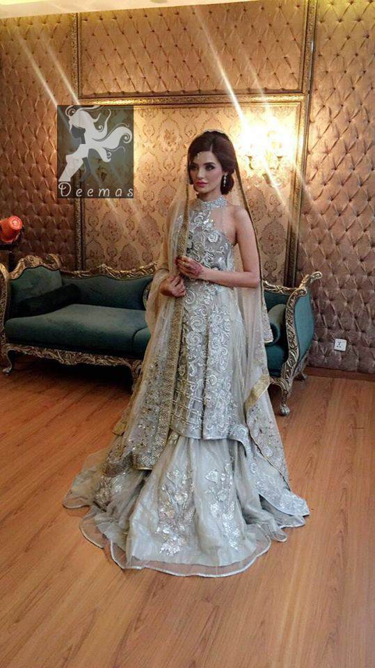 This outfit is a timeless beauty. It is heavily embellished with silver kora, dabka, sequins and swaronski crystals. This exquisite A-line frock is fully decorated with floral motifs patterns all over it. It is further enhanced with halter neckline.It comes with sharara which has small sized sprinkled floral motifs all over. This Outfit is beautifully coordinated with matching dupatta with heavy embroidered borders and finished with piping.
