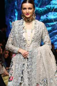 This outfit is a timeless beauty. It is heavily embellished with silver gold kora dabka, Sequins and swarovski crystals. This exquisite Pishwas is fully decorated with floral motifs patterns all over it. It is further enhanced with multiple colored Foral thread embroidery. The applique border of pishwas is ornamented with small silver pearls.