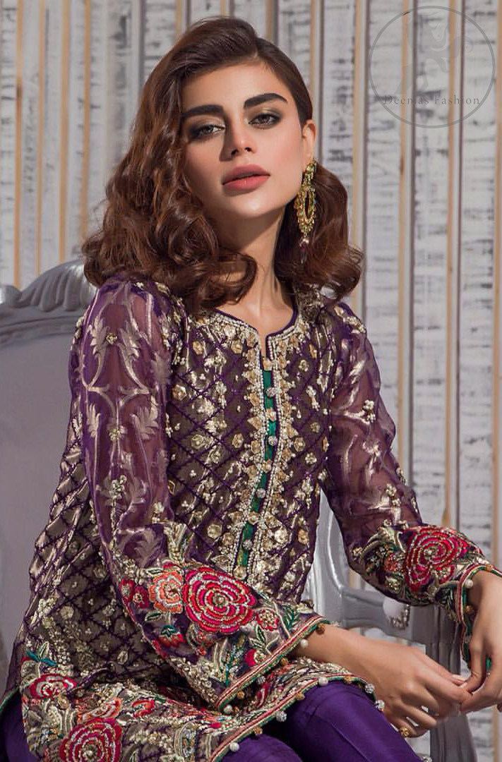 This outfit is beautifully sculptured with multiple color floral embroidery. The iridescent organza shirt is adorned with self print criss cross patterns. It is embellished with dull golden kora, dabka, tilla, and sequins work. Neckline is adorned with embellishments. It is artistically coordinated with chiffon dupatta with sprinkled sequins all over it. It comes with purple straight trousers.
