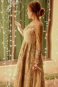 Delicately crafted and personifying chic elegance with an element of grandiose. This pretty gold embroidered frock done with kora dabka, tilla, diamante and sequins. Hemline edges are fully decorated with pearls. It comes with Brocade Pajama and Net dupatta sequins spray all over.