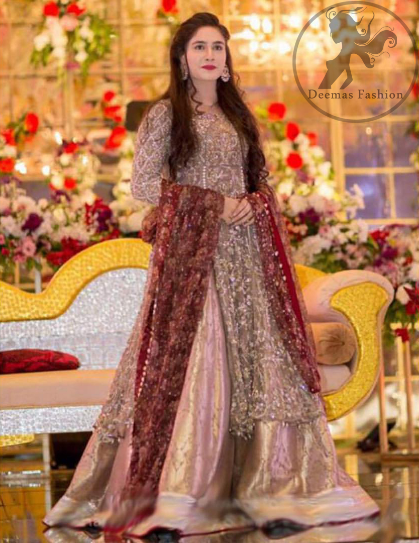 This dress is beautifully decorated with floral embroidery. This exquisite A-line front open shirt is fully decorated with floral and different motifs pattern all over it. It is highlighted with kora, dabka, tilla, sequins and pearls. Front open shirt allured with embellishments. It comes with net sharara. It is coordinated with net dupatta which is allured with delicate tassels.