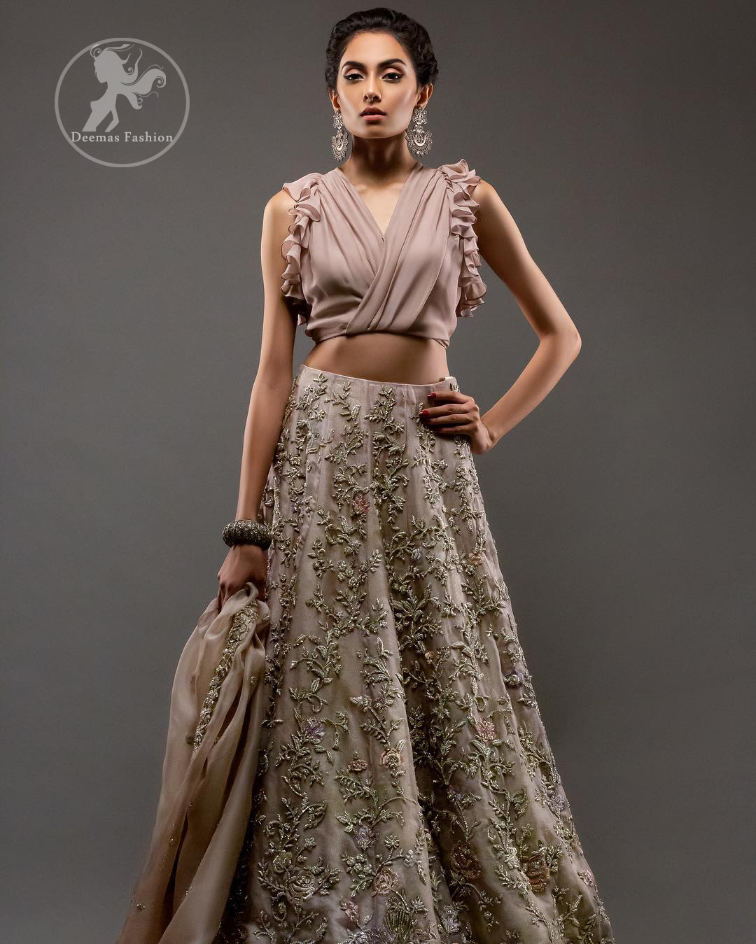 Commemorating the juxtaposition of traditions and modern sensibility with sensuous silhouettes and a subtle pastel palette. Feel glamorous in this stylish blouse paired up with rodeo dust lehengha. The lehengha is delicately crafted with golden kora dabka, tilla and kundan work. Multiple colored floral motifs enhanced the beauty of this outfit. It is coordinated with scalloped embellished border dupatta, also having sprinkled sequins on the ground.