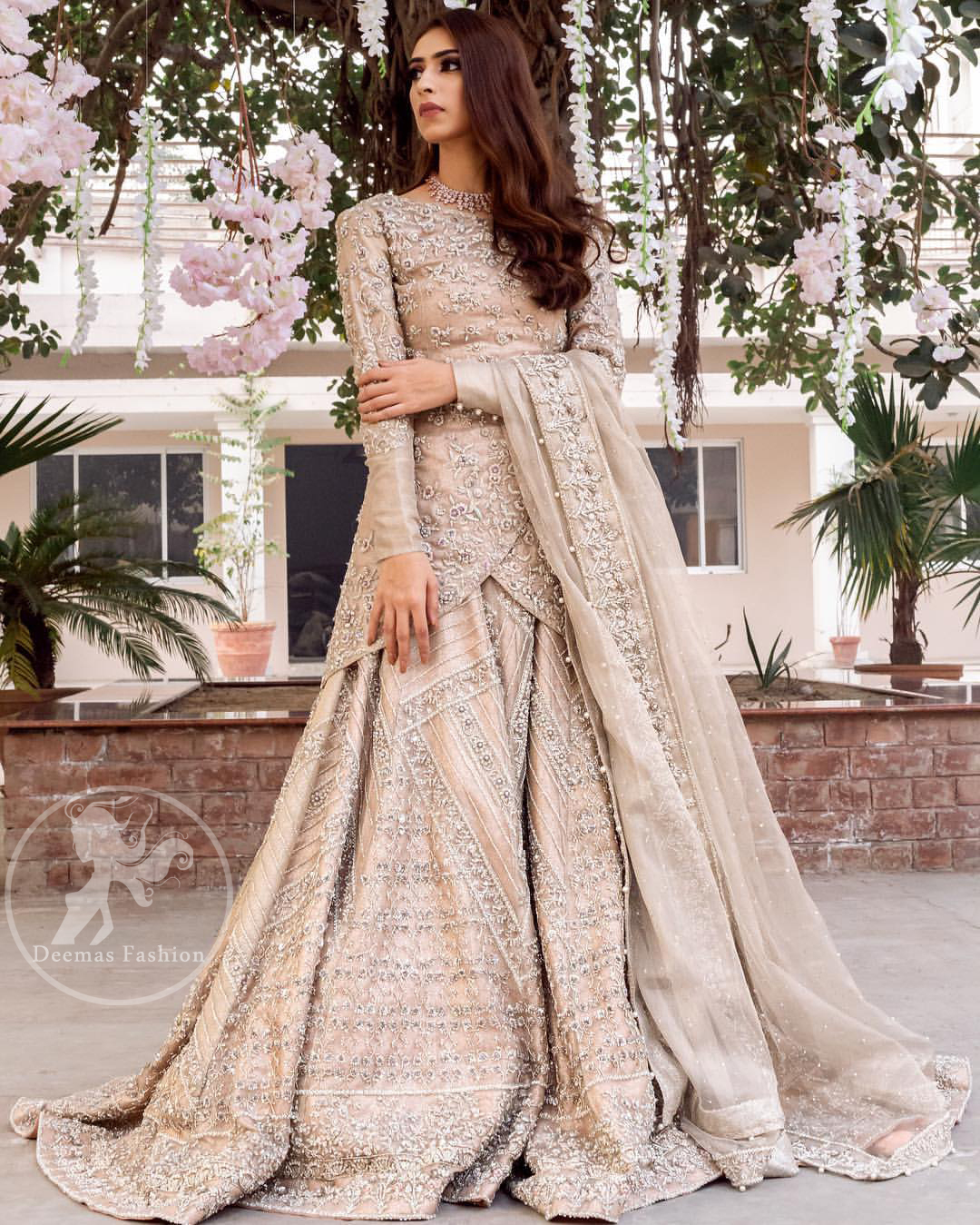 This outfit is adorned with kora, dabka, tilla, sequins and pearls. It is decorated with floral embellishments. It is overlapping shirt which adds to the look. It comes with heavy embellished lehengha allured with geometrical pattern all over it which has thick border on hemline. Tissue dupatta accompanies the garment. The dupatta has embellished borders on all four sides and small floral motifs all over it. The garment is lined with medium silk.