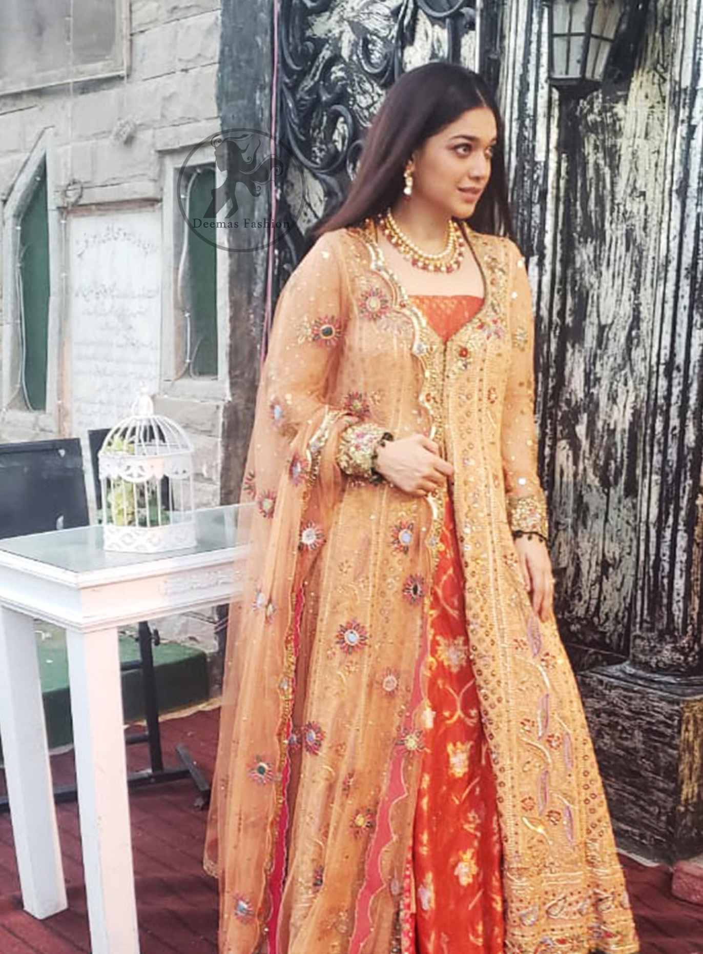 Go for this trendy dress and capture the attention in this persian red inner gold sand gown with kora, dabka and kundan embroidery. The gown is decorated with different size floral motifs and multiple color thread embroidery. Inner is enhanced with geometric pattern details on the bottom. Paired up with brocade straight trousers. It is coordinated with chiffon dupatta which is sprinkled with sequins and small floral motifs all over it. Further it has scalloped borders on all four sides embellished with zardosi work.