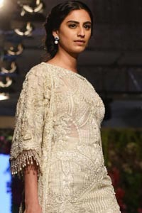 Go for this trendy dress. This dress is heavily embellished with floral and geometric styled embroidery decorated with silver kora, dabka, swarovski and pearls. Gown is enhanced with scalloped border decorated with tassels finishing. Third quarter sleeves are embellished with floral motifs all over along with tassels at the end. Trousers is magnificently decorated with cut-work. It is coordinated with tissue dupatta which is sprinkled with sequins all over it.
