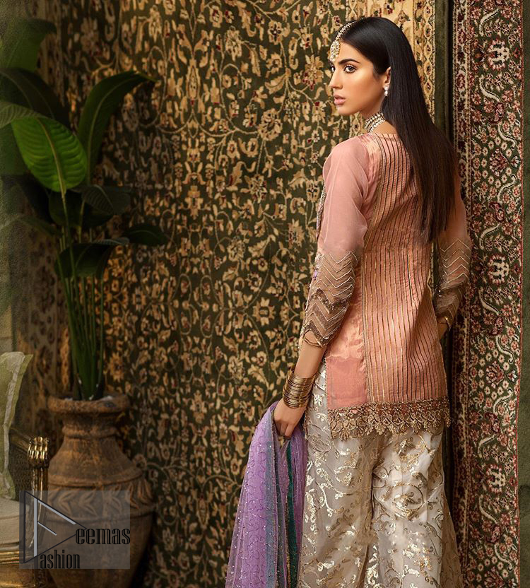 Add some super cool twist to your look with this outfit on your nikah. Gussy up in this luxuriously designed shirt emboldened with intricate embroidery along with beautiful rich patterns and delicate applique details at the daaman. Furthermore this super stunning shirt is made of rich floral embroidery which is further enhanced with zardosi work. Having full length sleeves adorned with scalloped finishing. Style it up with artfully coordinated ivory sharara finessed with lace and applique details at the bottom. The outfit is beautifully coordinated with light purple dupatta with embellished lace borders on all four sides and scattered sequins all over.