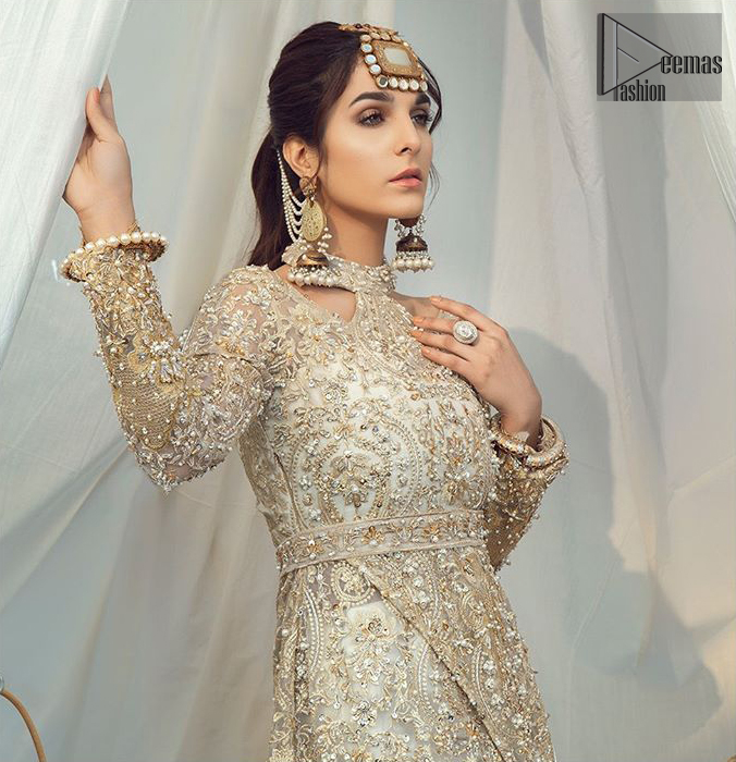 Brighten up your look with this glamorous halter neckline maxi perfect for your wedding day or evening ensemble. This glamorous attire accentuated with finest zardosi work and cut work borders. The bottom of the maxi has small circular motifs adorned with golden pearls and detailed scalp border gives a perfect ending to this maxi. Having full length sleeves ornamented with kora, dabka and tilla embroidery with sequins spray all over. Style it up with artfully coordinated ivory straight trousers finessed with organza details at the bottom.