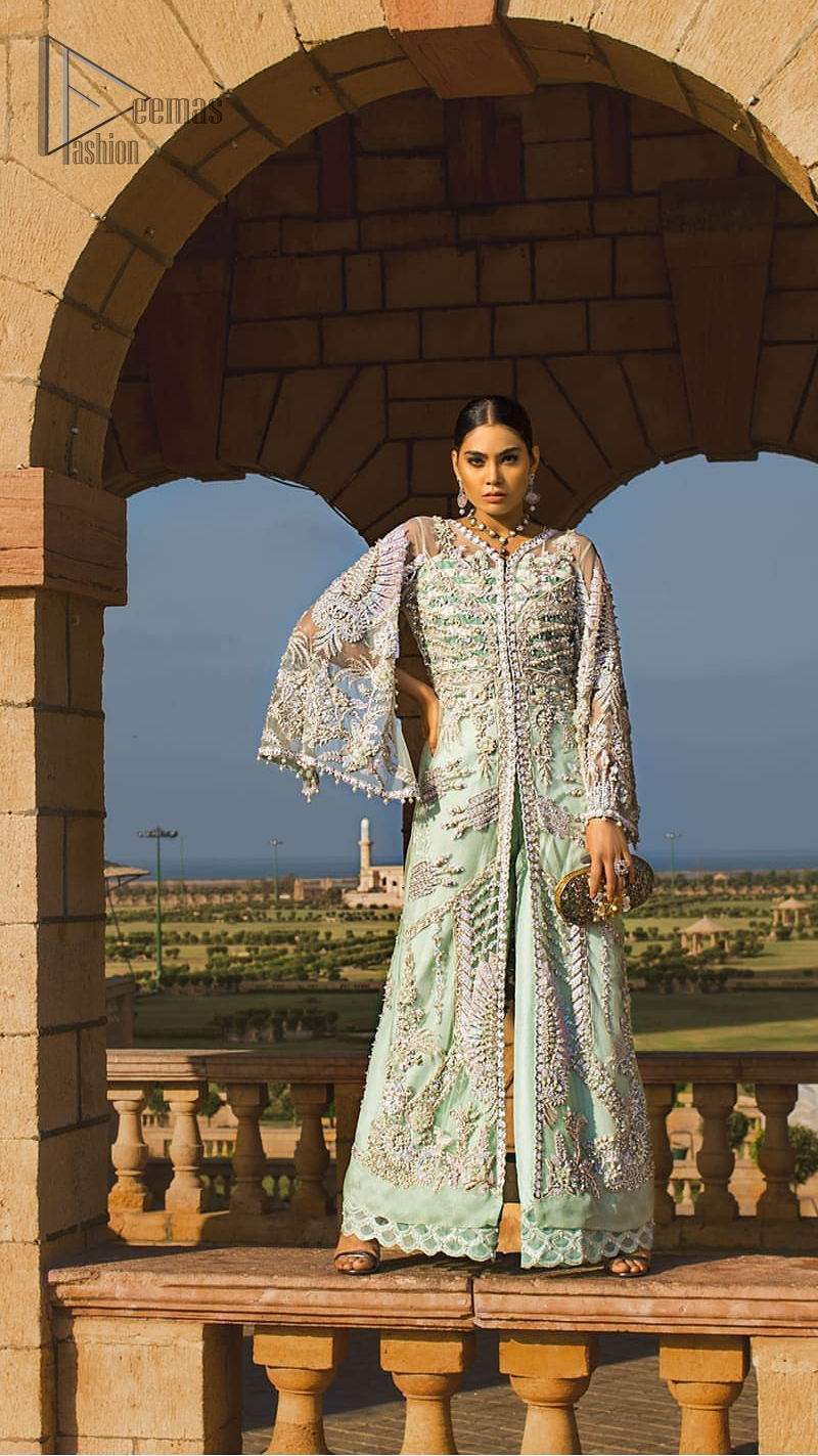 Take a step towards refreshing your wardrobe with aqua front open gown and palazzo pants. This front open gown is perfected with loaded light golden and silver work. The front of the gown is heavily embellished with different styles motifs and rich embellishment on bodice. Furthermore the back of the gown and bell sleeves are also decorated with detailed embroidery and dangling balls. The palazzo pants with it is made of raw silk fabric with lace detail on the bottom. The outfit is coordinated with aqua organza dupatta sprinkled with sequins all over.