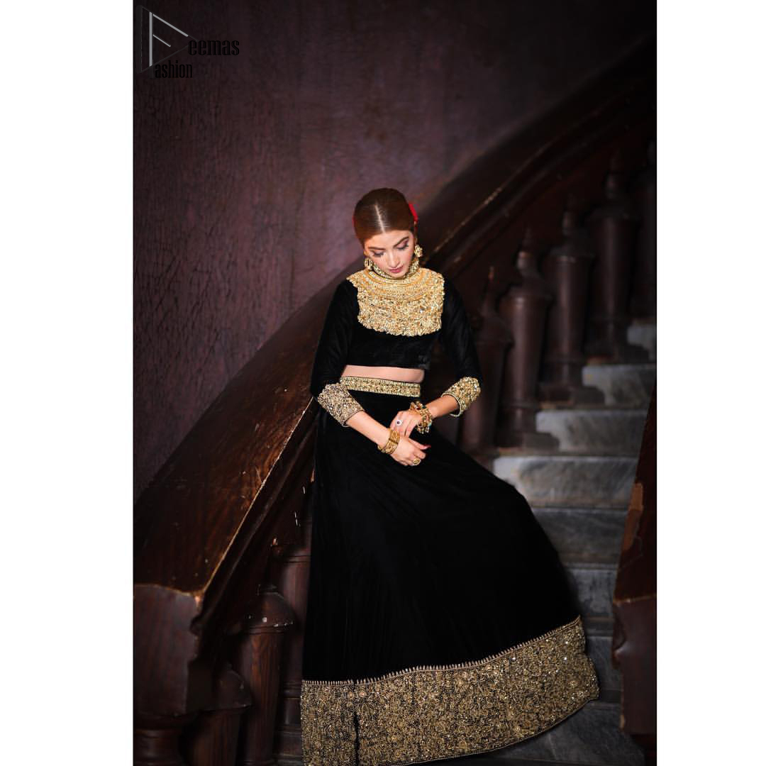 Embrace the season of festivities with this beautiful dress. This elegant ensemble turns timeless piece into a chic fantasy. The halter neck blouse is delicately hand crafted using the finest old age techniques and materials including kora, dabka, tilla, sequins, stones, and crystal. The sleeves are embellished with a thick embroidered border. Lehenga comprises of thick embroidered bottom to give it a regal look. It comes with a black net dupatta with sequins sprayed all over it .