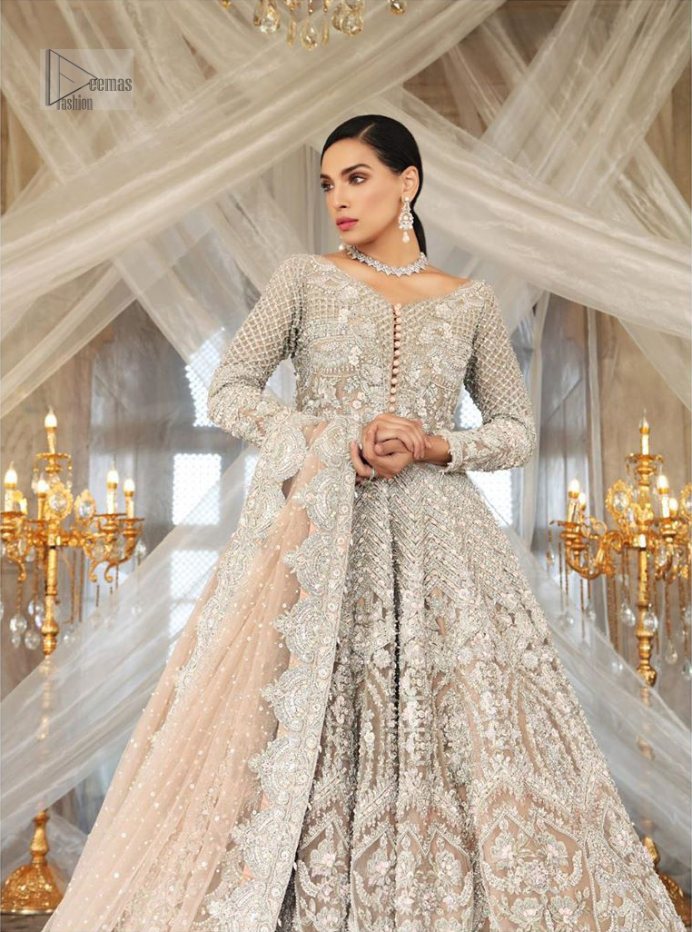 Paint a picture of pure elegance with this beautiful pishwas. This dress is beautifully sculptured with floral embroidery, adorned with geometric patterns embellished with silver kora, dabka, pearls and sequins work all over. The detailed scallop border gives a perfect ending to this pishwas. The lehenga is emphasized with embellished bottom that gives perfect ending to thisoutfit.It is coordinated with net dupatta sprinkledwith chann all over and finished with embroidered border on four sides which makes this outfit more beautiful.