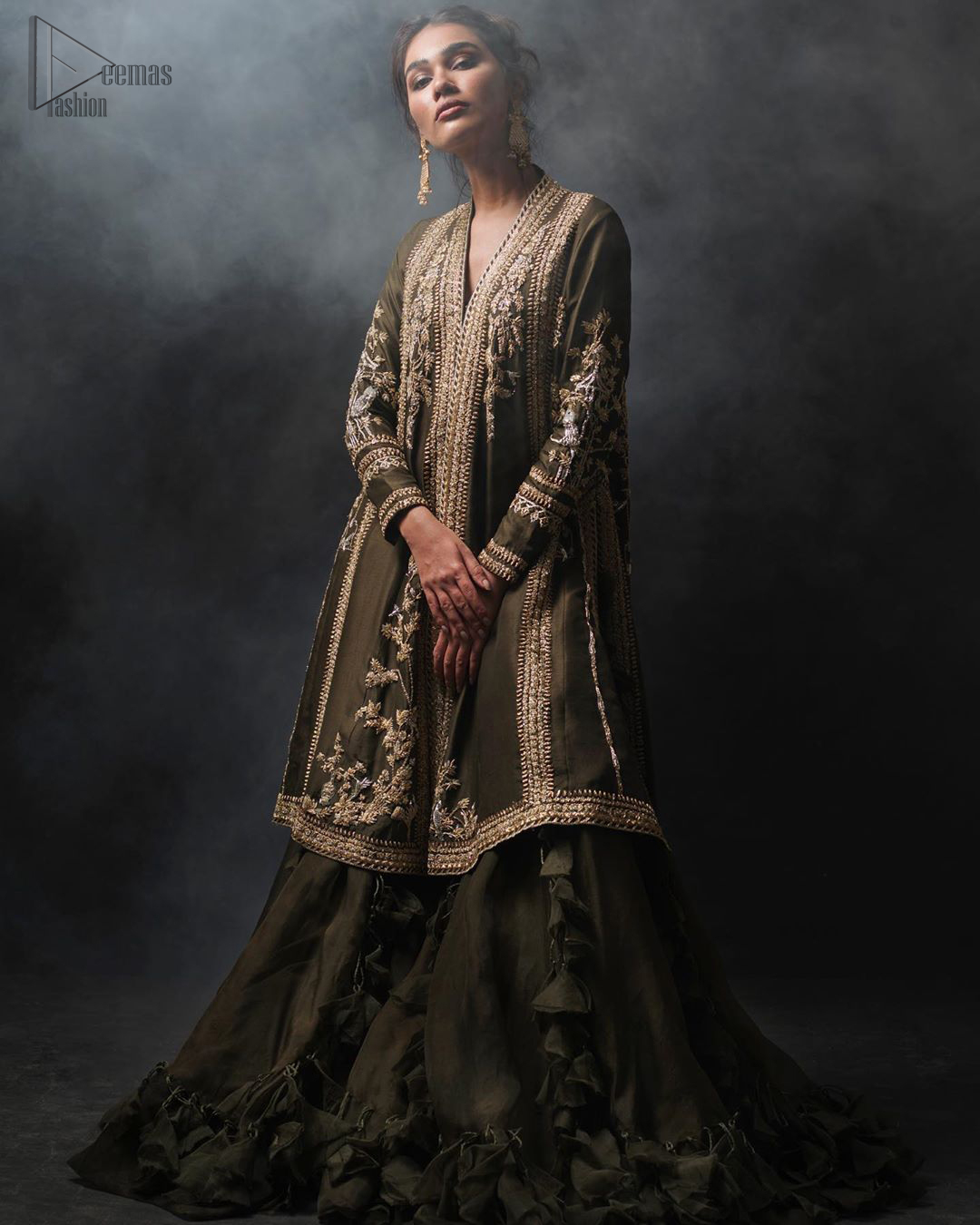 Discover your inner charm with this ravishing front open shirt adorned with golden embellishment. A delicate arrangement of hand embellished floral bunches with zardozi work. Full sleeves and side slits are also decorated with kora, dabka, tilla and sequins work all over. It is coordinated with frilled sharara gives it a perfect look. Style it up with olive green dupatta sprinkled with sequins.