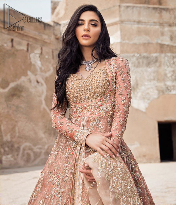 This garnet ensemble is sure to make you look like glamorous royalty with immaculate work covering every inch of the frock. The bodice of the frock is heavily embroidered with champagne zardozi work. Furthermore the hemline is ornamented with geometric patterns. It is coordinated with peach and light pink lehenga with a flowing train embellished with light golden and champagne embroidery and scattered floral motifs in a sequence. this is an ensemble that deserves to be flaunted. Style it up with light pink dupatta having four sided embroidered border.
