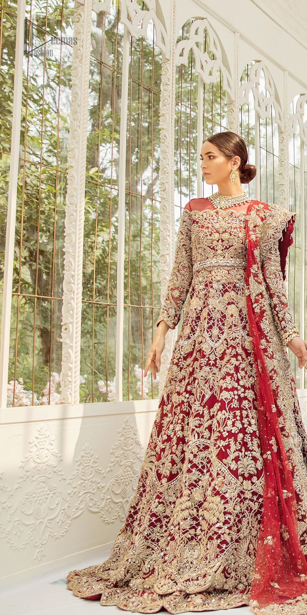 This bridal dress is perfect for your big day. Our bride makes a statement in this stunningly floraison, perfect blend of glamour and tradition with outstanding craftsmanship and gorgeous detailing. This floor length maxi is beautifully sculptured floral jhaal, floral bunches and thick scalloped hemline done with light golden kora, dabka, tilla and sequins embroidery. Exude elegance with red lehenga finessed with beautiful embellished scalloped bottom with zardosi work. The red net dupatta with chann and finishing all around the edges makes the look complete.