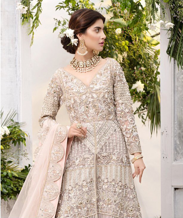 Make a special day even more magic with our exquisite flora bridal maxi dress. Discover classic look in this outfit for a traditional style, with delicate detailing and intricate accents for a subtle yet sophisticated look, having full sleeves with zardozi details. Furthermore the hemline is emphasized with a large central motif and small motifs around it that gives perfect ending to the outfit. It comes with tea pink lehenga with zardozi details on the bottom. Paired with light purple net dupatta sprinkled with sequins and four sided embellished border that gives the right amount of glamour to the outfit.