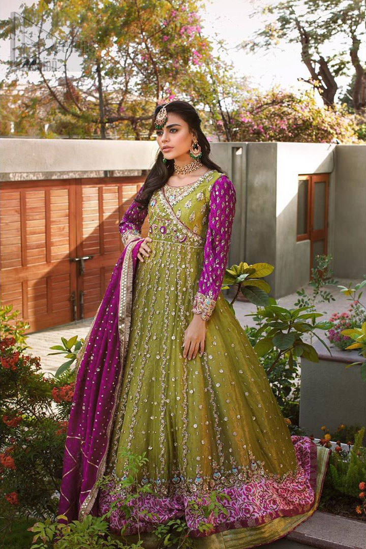 Nothing speaks of femininity and class louder than this mehndi outfits for bridesmaids. The sequinned whimsical florals embroidered across the flattering bodice in this ethereal frock is sure to turn heads in every room you walk into. The pairing of champagne zardozi work with parrot green fabric is an artist's dream colour palette. The frock hemline is emphasized with banarsi applique details that gives perfect ending to this outfit. It comprises with matching tissue lehenga. The magenta organza dupatta with chann and gota work, finishing with kiran lace all around the edges makes the look complete.