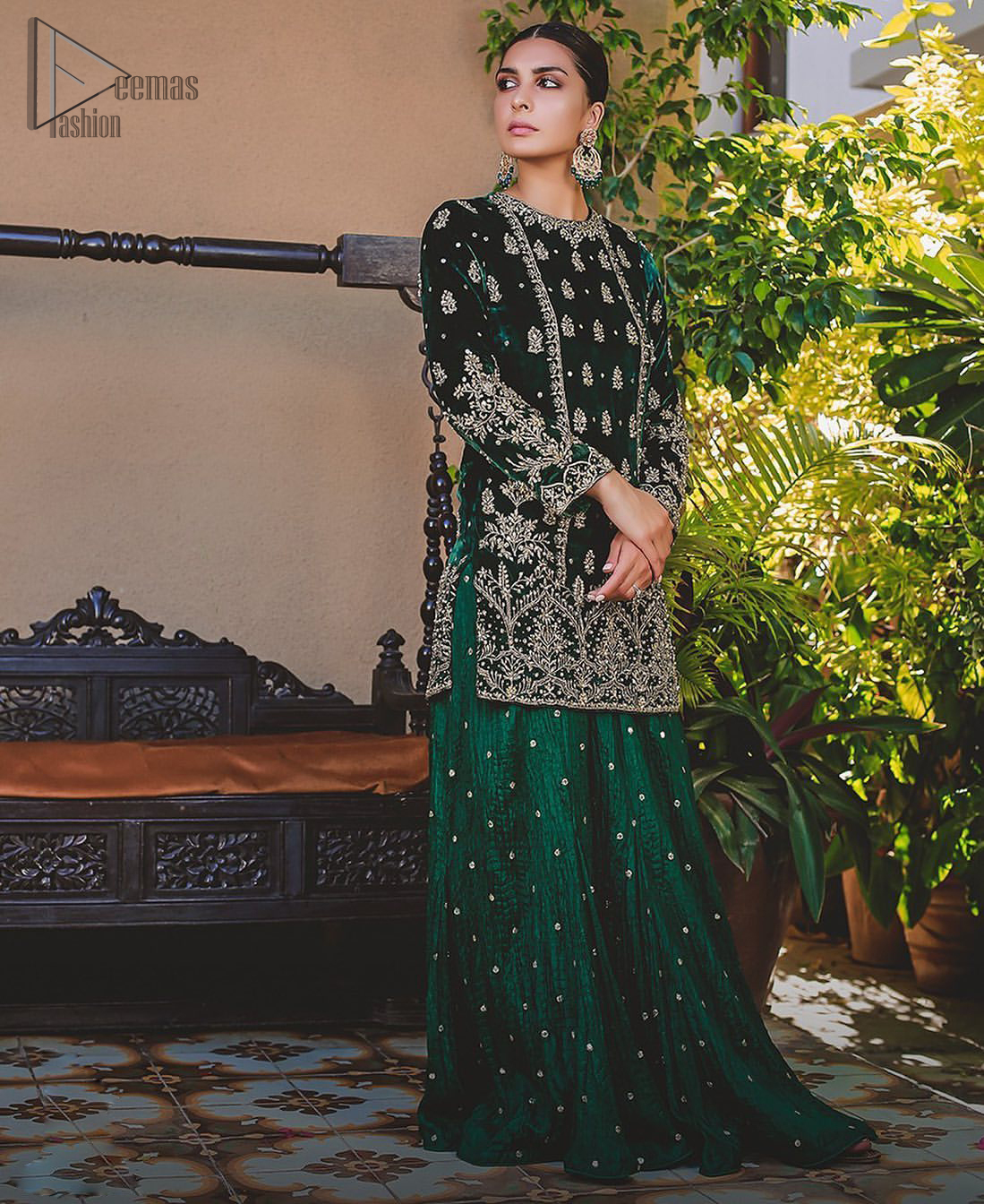 This mehndi outfit is a true example of decorative and ornamental expression stylized in a contemporary way. The dress comes with a bottle green velvet shirt with beautiful embellished motifs on the ground and vertically worked lines and it finished with a thick embellished border with silver zardozi work. Pair it up with bottle green crushed sharara adorned with scattered sequins all over. To complete the look, go with chiffon dupatta decorated with sequins spray all over.