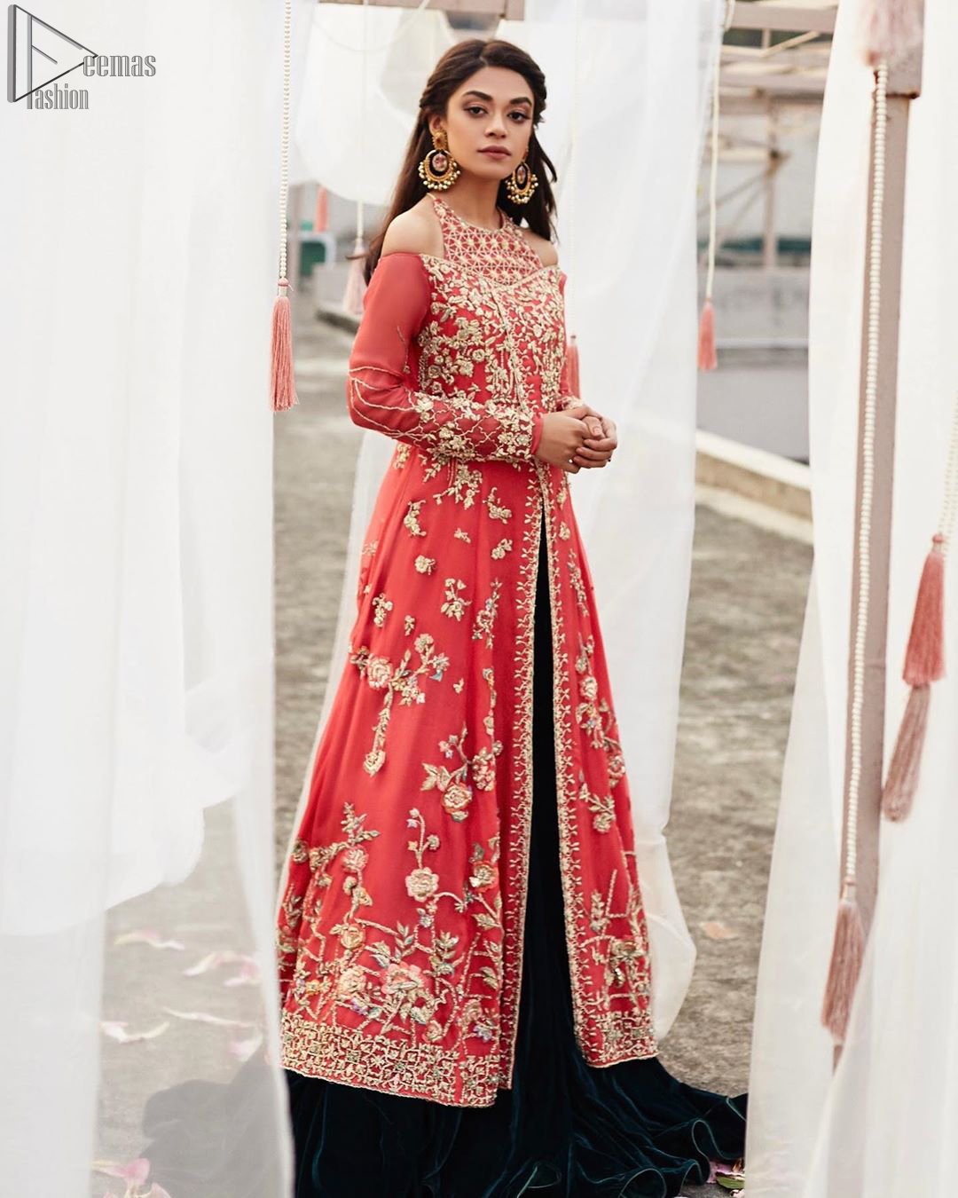 This outfit brings drama and playfulness to traditional frock and Sharara with a modern approach. Drape yourself to perfection for the classic affair in this flattering front open ensemble festooned with intricate zardozi hand embroidery work and motifs. The frock is furthermore adorned with halter neckline and comprises with overlaped bodice. Embellishment is done with zardozi embroidery in silver color. This outfit is comprises with bottle green velvet sharara and coral chiffon dupatta with sequins spray all over.