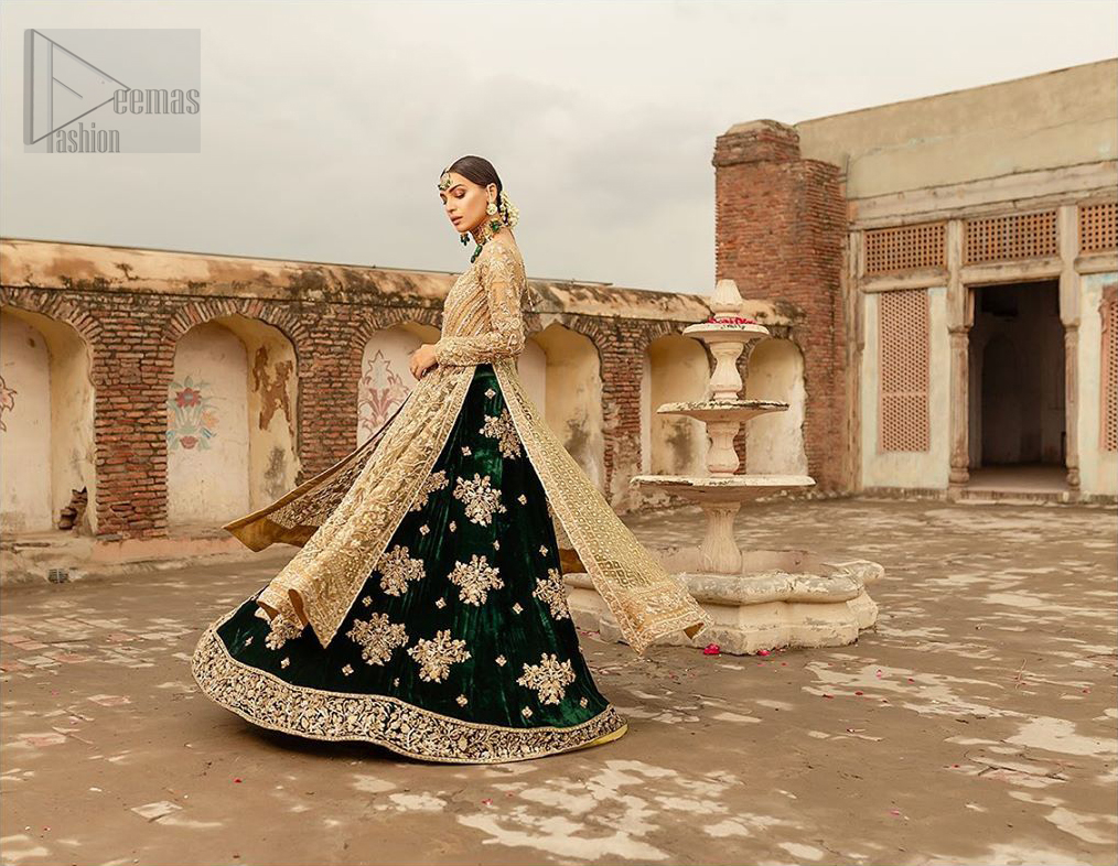 The new season is all about making a statement. Make your moment memorable being a queen in our fawn front open pishwas intensified with voguish sleeves, floral pattern all over and finished with thick embroidered border. The back of the shirt is also enhanced with criss cross patterns filling with beads. Pair it up with bottle green velvet lehenga emphasized with scattered floral motifs and intricate zardozi detailing at the bottom. Dupatta is decorated with vintage froral and finished with embroidered scalloped border on four sides which makes this outfit more beautiful.