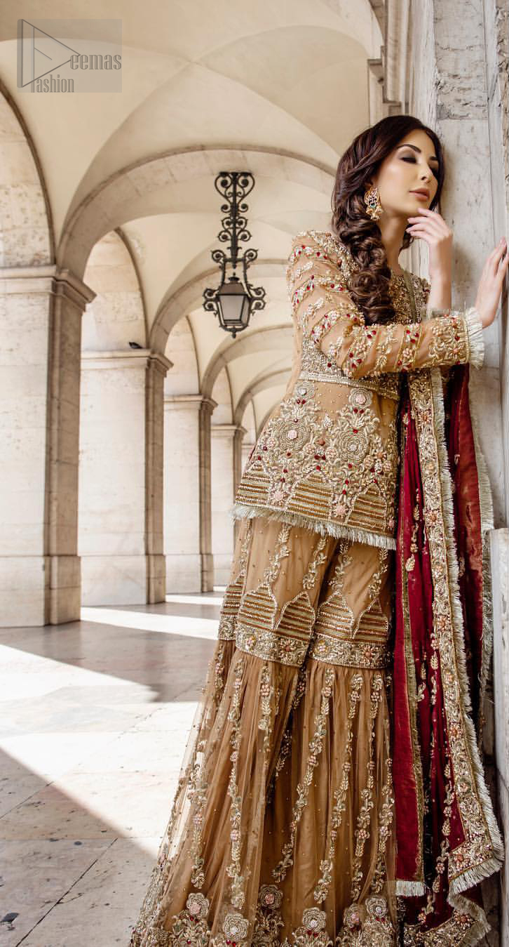Picturing your bridal in a glowing fawn color. Featuring beautiful handwork, this outfit has a delicate arrangement of hand embellished geometric patterns with pearls and crystals on the bottom. Refined craftsmanship is at its best with hand embellished bodice which is laden with zardozi work. This outfit is paired with organza gharara with embroidered bottom and kiran lace, and maroon dupatta ornamented with geometric patterns along the length, making it a statement piece. Furthermore it is also enhanced with kiran lace on all four sides.