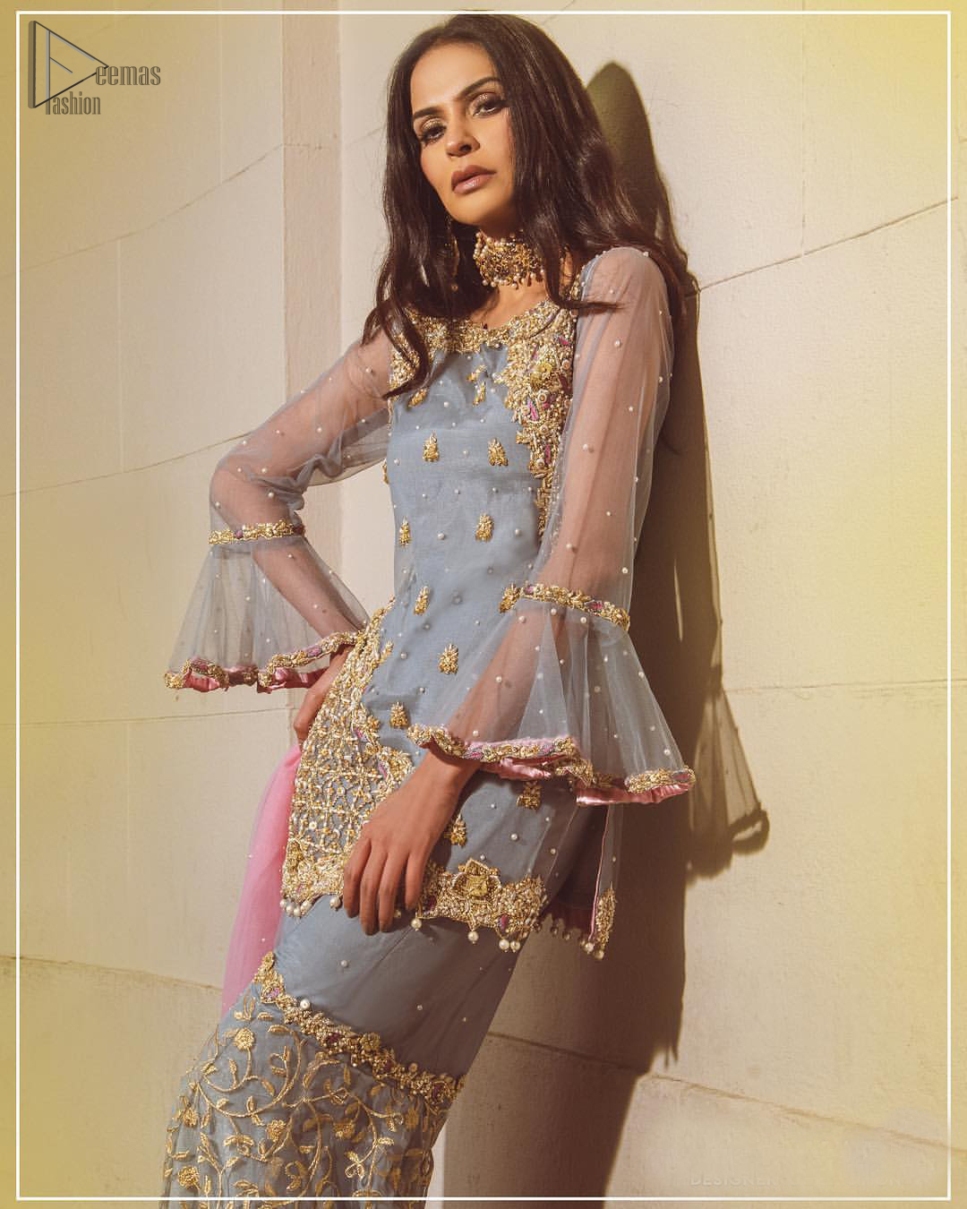 Embrace the season of festivities with this beautiful dress. The chic yet elegant outfit is decorated with golden embroidery, embellished neckline and tiny floral motifs. Borders are even more enhanced with golden zardozi detailed patterns and finished with scallops and dangling balls. Pair it up with gray sharara highlighted with floral jaal and scalloped bottom done with golden kora, dabka and tilla work. The look is complete with pink net dupatta sprinkled with sequins all over.