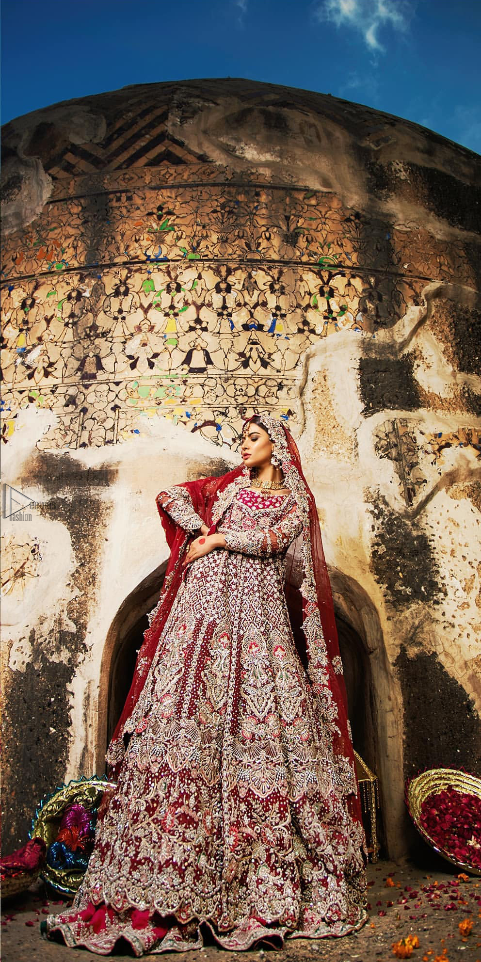 Complete your big day with the perfect dress in our selection of stunning wedding dresses. This artisanal piece is rendered in grace and timelessness. The bodice with a sweetheart neckline is adorned in richly zardozi work with fabulous sparkle. The rest of the dress is beautifully crafted with floral motifs, geometric patterns and embroidered lines along the length. Pair it up with a red lehenga emphasized with multiple colour kora, dabka, tilla and sequins work. Furthermore, the outfit is also adorned with sequins spray all over the ground. Complete the look with an artfully coordinated dupatta having embellished scalloped borders and scattered tiny floral motifs.