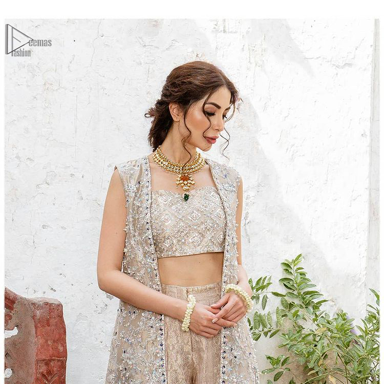 This sleeveless blouse follows an open front, lined beautifully with geometric patterns. A traditional design of mesmerizing silver embroidery intensifies its charm. Pakistani Party Dress - Beige Open Shirt n Blouse - Palazzo Pants.