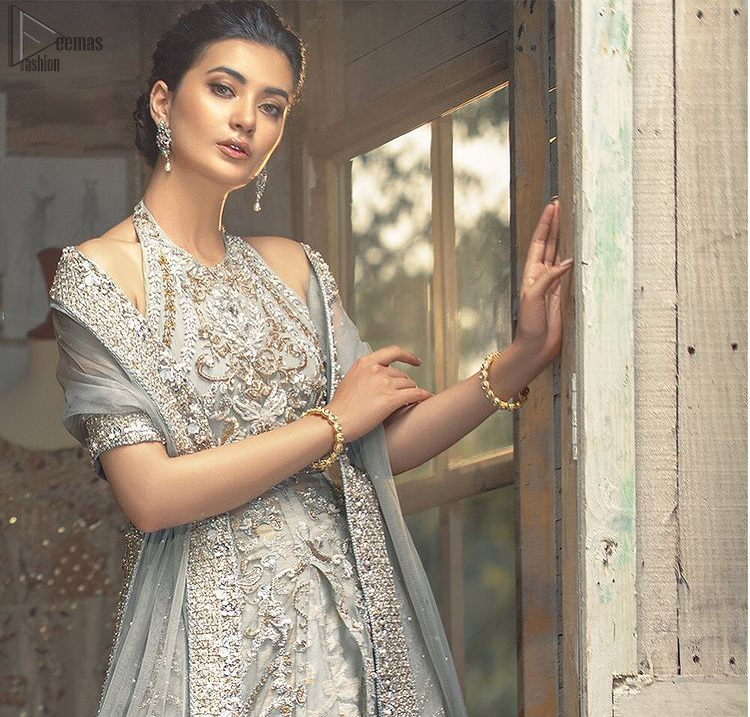 Nikah Wear - Light Grey Halter Neck Gown Lehenga. The floral and the flowery climber networks on fully embellished Halter neck and blouse has exquisitely exaggerated in the beauty of the costume making it very unique. The bottom lehenga with Fixed Waist Belt With Side Zip Closure is composed of Katan Banarsi Jamawar fully embellished with flowery climbers with Light Gray colour tone; being exquisitely beautiful in perfecting the complete outfit having a unique fabric and double flare lehenga that is in stellar combo with the blouse with finished edges and Dupatta sideways carried beautifully by the bride with organza fabric and Heavy beautiful golden and Grayish lace on all four bordered finished sides and dabka work on the net inside of the gorgeously made dupatta, whole this costume has its own unifying feature such as 100 % imported high quality overall highly embellished fabric making it the best choice to have by you on your big day.