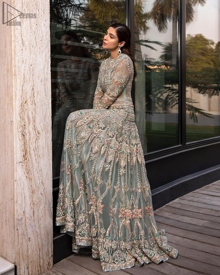 Pastel Green Large Flared Anarkali - Pakistani Wedding Gown. The bottom part of this amazing outfit comprises a lehenga with Fixed Waist Belt With Side Zip Closure. The Ivory i.e silver general embroidery with floral motifs and multicolour embroidery network on organza with finished embellished edges has its own impact. The Dupatta carried sideways have also tissue fabric with embellished four sides and finished edges. Whole this embellishment, the gorgeousness of the costume comes to the spectator noticing eye because of another unifying feature of this outfit that it is 100% imported, pure highest quality fabric.