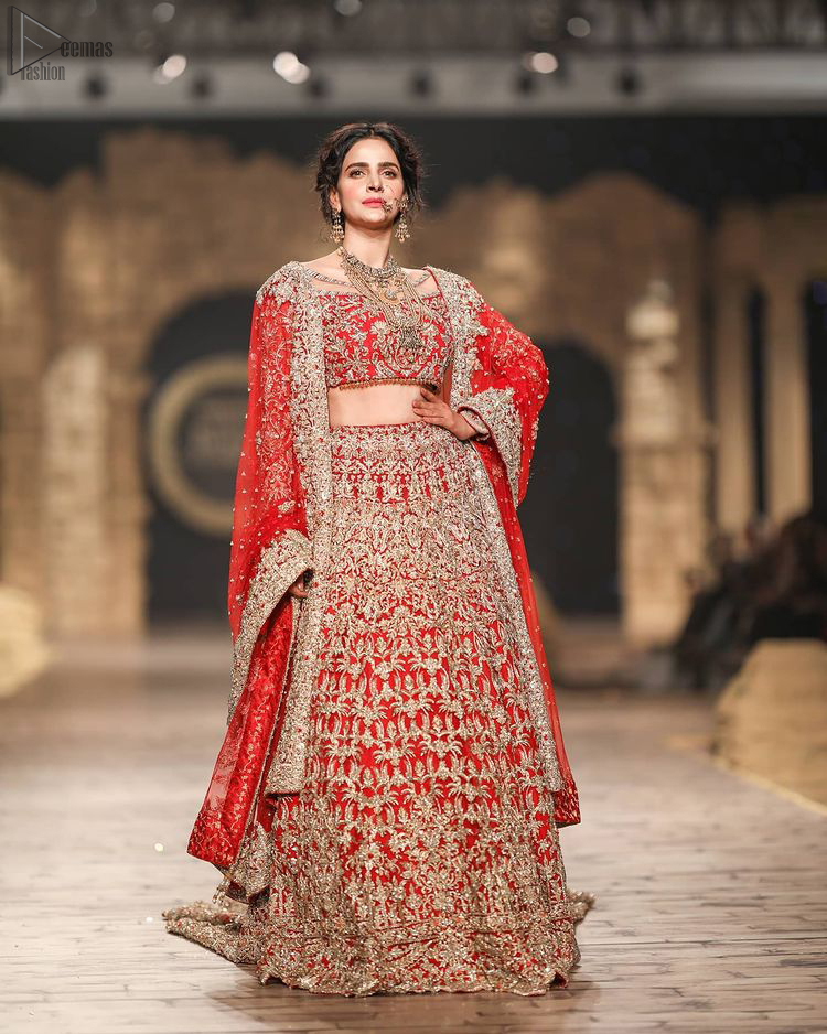 Pakistani Wedding Wear having Red Short Blouse Lehenga. The dress constitutes a pure organza based blouse with a boat-shaped neckline, followed by a beautiful Lehenga.