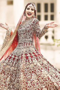 This bridal outfit is perfect for your unforgettable day. This exceptionally detailed dress is cut in a seductive fit and flare silhouette that's sure to turn heads. Featuring a delicately embellished neckline highlighted with zardozi detailing and intricately embroidered borders. This technique gives our garments a unique look and helps to sustain a traditional craft carried out by skilled artisans across Asia. The lehenga is heavily laden with golden kora, dabka, tilla, sequins and beads work and also beautified with scalloped borders. Pair it upwith heavily embroidered organza dupatta that gives the right amount of glamour to the outfit.