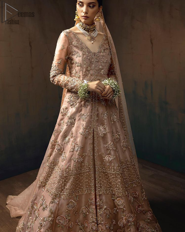 Pictured in a fabulous outfit, Chic and sophisticated perfectly describe this simply stunning wedding dress. The shirt is meticulously embellished with antique brass zardozi work. The sequinned whimsical florals embroidered across the flattering bodice in this ethereal gown is sure to turn heads in every room you walk into. Balance the look with a tea rose tissue lehenga. Pair it up with an organza dupatta which is sprayed with sequins glorifying its grace. Moreover, it is also enhanced with a four-sided embellished border that increases the enormous adornment of the whole outfit.