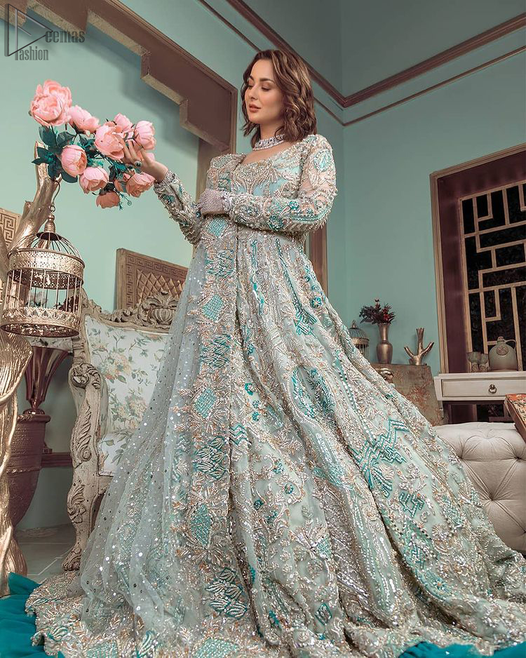 This style-savvy bride totally pulled off our classic bridal wear with unmatchable grace-giving major bridal goals. Featuring beautiful handwork, this outfit has a delicate arrangement of hand-embellished floral patterns with pearls and crystals along the length. Refined craftsmanship is at its best with hand embellished zardozi work elegantly all over the outfit. Frilled on the bottom of the maxi makes the outfit look like nothing but a dream. This outfit is paired with an organza dupatta with embroidered border and raw silk churidar pajama, making it a statement piece.