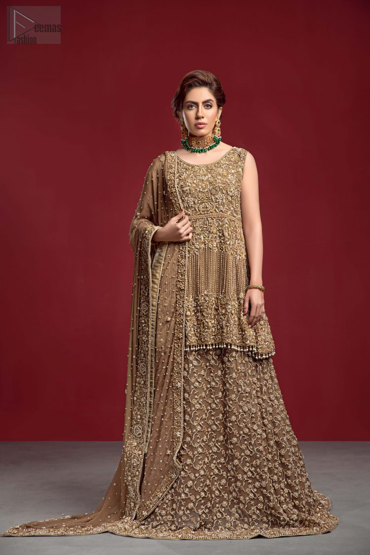 Captured in a traditional silhouette, The bridal stands out due to its uniqueness and the perfect fusion of modern cut and traditional embroidery. This dress is beautifully decorated with heavy embroidery. It is highlighted with kora, dabka, tilla, sequins and pearls. The peplum is enhanced with zardosi work all over and tassels on the hemline. It comes with a full embellished lehenga adorned with a fully embellished back train. It is coordinated with an organza dupatta which is sprinkled with pearls all over it. It is further furnished with a four-sided embroidered border.